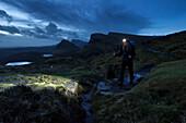 Young woman with headlamp hiking in twilight, Quiraing, Trotternish peninsula, Isle of Skye, Scotland, United Kingdom