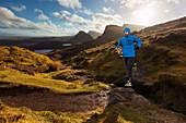 Young man running on a trail, Quiraing, Trotternish peninsula, Isle of Skye, Scotland, United Kingdom