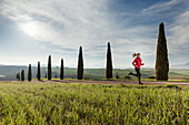 Young woman jogging along a path with cypresses, Tuscany, Italy