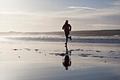 Young woman jogging at beach, Dunnet Bay, Caithness, Scotland, United Kingdom