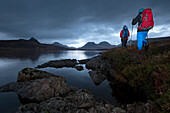 Young couple with backpacks hiking at Loch Bad a Ghaill, Stac Pollaidh, Cul Beag, Sgorr Tuath and Ben Mor Coigach in background, Assynt, Scotland, United Kingdom