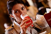 Woman enjoying a drink inside a bar, Galleria Vittorio Emanuele II, Milan, Lombardy, Italy