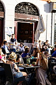 Young people sitting in front of a bar, Navigli quarter, Milan, Lombardy, Italy