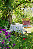 Garden still life with table and chairs and summer flowers, Freiamt, Emmendingen, Baden-Wuerttemberg, Germany