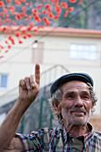 Cheerful elderly man raising his finger at a festival honoring the patron saint, Ponta Delgada, Madeira, Portugal