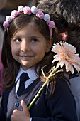 Girl with floral headdress, holding a flower at the childrens parade at the Madeira Flower Festival, Funchal, Madeira, Portugal