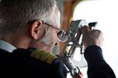 Cruise ship MS Deutschland (Reederei Peter Deilmann) chief mate Elmar Muehlebach with sextant, near King George Island, South Shetland Islands, Antarctica