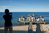 Woman taking a photograph of Sellin pier, Sellin, Ruegen island, Baltic Sea, Mecklenburg Western-Pomerania, Germany