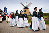Women in traditional frisian costumes, in front of a windmill, Nebel, Amrum island, North Sea, North Friesland, Schleswig-Holstein, Germany