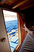 Person lying in a bed on a boat with view on the sea, Hvar, Dalmatia, Croatia