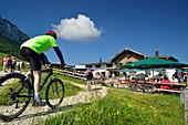 Mountainbiker arriving at Steinlingalm, Kampenwand, Chiemgau Alps, Chiemgau, Upper Bavaria, Germany