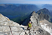 Woman ascending on fixed rope route to Zugspitze, lake Eibsee in background, Wetterstein mountain range, Upper Bavaria, Bavaria, Germany