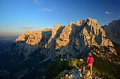 Woman looking mountain scenery from Stripsenkopf, Zahmer Kaiser, Kaiser mountain range, Tyrol, Austria