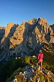 Woman looking at mountain scenery from Stripsenkopf, Zahmer Kaiser, Kaiser mountain range, Tyrol, Austria