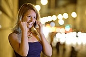 Young woman phoning with a mobile phone, Munich, Upper Bavaria, Bavaria, Germany