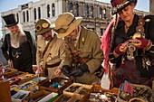 Joy of fossicking for a treasure, men and women in Victorian costume search for brass buttons, Victorian festival, historic precinct, Oamaru, Otago