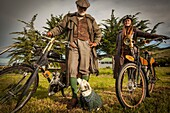 Lady and gentleman in Victorian costume with antique bicycles with small engines, Victorian festival, historic precinct, Oamaru, Otago