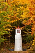 A hillside lighthouse beacon with fall foliage color in Munising, Michigan, USA
