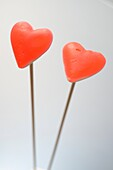 Two red hearts over wooden poles, gray background.