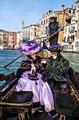 A masked couple in a gondola at the carnival in Venice, Italy, Europe