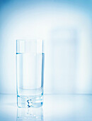Glass of drinking water isolated on light blue background