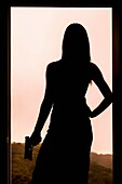 Silhouette of a woman holding a gun while standing in a door frame