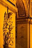 Detail on Arc de Triomphe at night, Paris France