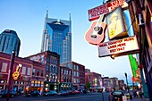 The AT&T building towers over the historic bars and honky-tonks along lower Broadway in Nashville Tennessee USA