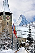 Snowy walkway leading to church with the Matterhorn looming beyond, Zermatt Switzerland