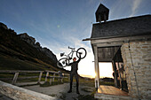 Mountainbiker at the Steinling chapel under the Kampenwand, Chiemgau, Upper Bavaria, Bavaria, Germany
