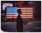 Businessman Walking in Front of Neon American Flag, Times Square, New York City, USA