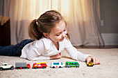 Girl Playing on Floor with Miniature Cars and Trucks
