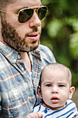 Man with Aviator Sunglasses and Beard Holding Infant Son, Outdoor