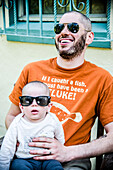 Bearded Father with Sunglasses Smiling and Holding Infant Son Wearing Sunglasses, Outside