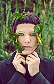 Young Man With Branch of Green Leaves Wrapped Around Face