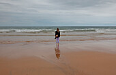 Young Woman on Beach Looking out to Sea, Rear View