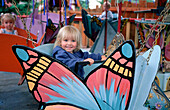 Young Blond Girl on Butterfly Ride at Amusement Park