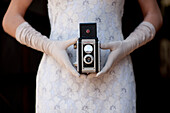 Woman in White Dress and Long White Gloves Sitting in Rocking Chair Holding Antique Camera