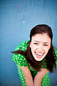 Laughing Young Woman in Green Dress with Polka Dots, High Angle View
