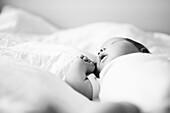 Newborn Baby in Onesie Sleeping on Bed