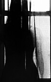Abstract Silhouette of Woman Standing Behind Curtain in Front of Window