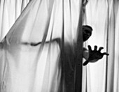 Screaming Man's Hand Reaching  out from Curtains