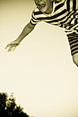 Young Boy with Striped T-Shirt and Shorts Jumping in Air