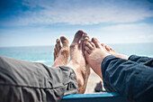 Couple's Sandy Bare Feet on Railing With Beach in Background