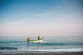 Two Men in Fishing Boat at Seashore