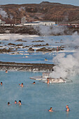 Bathers Enjoying The Hot Water Of The Blue Lagoon With, In The Background, The Svartsengi Geothermal Plant, Hot Springs And Silica Mud, Grindavik, Reykjanes Peninsula, Iceland