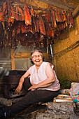 Elder Native Yupik Woman Sitting In Smokehouse Attending Drying Salmon Tuluksak Western Alaska