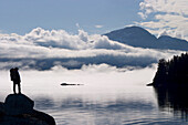 Composite: Silhouette Of A Backpacker Along The Shoreline Of Lynn Canal Near Juneau With Chilkat Mountains In The Background, Tongass National Forest, Inside Passage, Alaska
