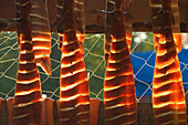 Traditionally Prepared Salmon Strips Hanging On Drying Rack W/Fishing Net Background Alaska Backlit