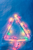 Abstract Christmas Tree Drawn In Fresh Blanket Of Snow With Christmas Lights Buried Underneath With Blue Toned Color Winter Alaska
